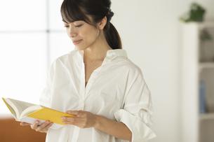 ソファーの前で立って読書をする女性の写真素材 [FYI04686081]