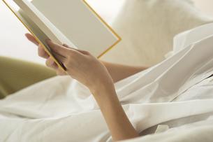 ソファーで読書をする女性の手元の写真素材 [FYI04686082]