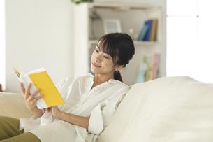 ソファーで読書をする女性の写真素材 [FYI04686083]