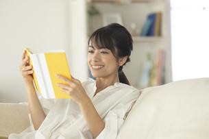 ソファーで読書をする女性の写真素材 [FYI04686084]