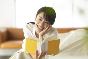 ソファーで読書をする女性の写真素材 [FYI04686086]