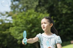 シャボン玉で遊ぶ女の子の写真素材 [FYI04686476]