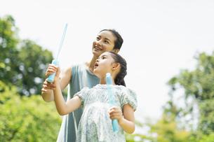 シャボン玉で遊ぶ親子の写真素材 [FYI04686488]
