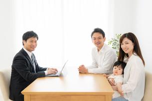 打ち合わせをするビジネスマンと家族の写真素材 [FYI04687284]