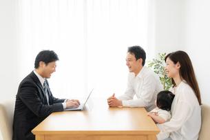 打ち合わせをするビジネスマンと家族の写真素材 [FYI04687287]