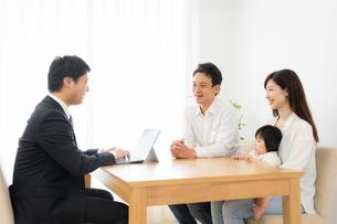 打ち合わせをするビジネスマンと家族の写真素材 [FYI04687295]