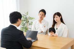 打ち合わせをするビジネスマンと家族の写真素材 [FYI04687302]