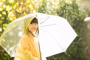 小さい女の子がレインコートを着て傘を持ちながら外で雨の日を楽しむの写真素材 [FYI04691253]