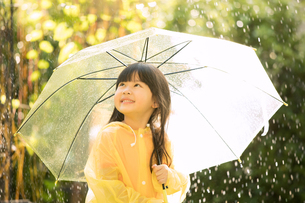 小さい女の子がレインコートを着て傘を持ちながら外で雨の日を楽しむの写真素材 [FYI04691257]
