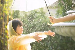 小さい女の子がレインコートを着て外で雨の日を楽しむの写真素材 [FYI04691294]