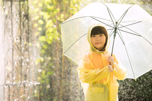 小さい女の子がレインコートを着て傘を持ちながら外で雨の日を楽しむの写真素材 [FYI04691311]