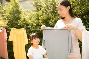 お母さんの洗濯物を干す家事を手伝う小さい女の子の写真素材 [FYI04691367]