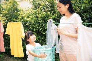 お母さんの洗濯物を干す家事を手伝う小さい女の子の写真素材 [FYI04691378]