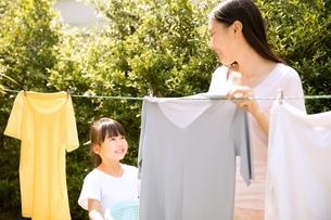 お母さんの洗濯物を干す家事を手伝う小さい女の子の写真素材 [FYI04691382]