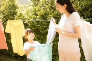 お母さんの洗濯物を干す家事を手伝う小さい女の子の写真素材 [FYI04691399]