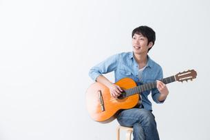 ギターを弾く男性の写真素材 [FYI04700129]