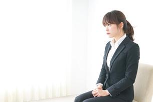 スーツでオフィスに座るビジネスウーマンの写真素材 [FYI04700249]