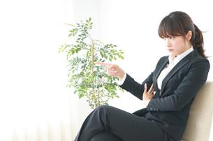 スーツでオフィスに座るビジネスウーマンの写真素材 [FYI04700258]