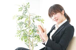 スーツでスマホを使うビジネスウーマンの写真素材 [FYI04700263]