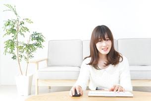 自宅でパソコンを使う女性の写真素材 [FYI04700440]