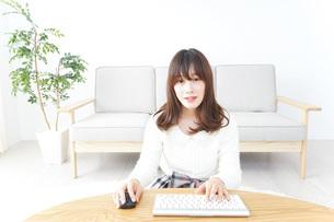 自宅でパソコンを使う女性の写真素材 [FYI04700447]