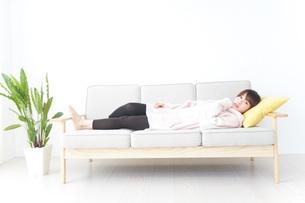 部屋でリラックスをする若い女性の写真素材 [FYI04700472]