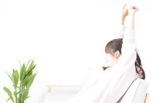 部屋でリラックスをする若い女性の写真素材 [FYI04700474]