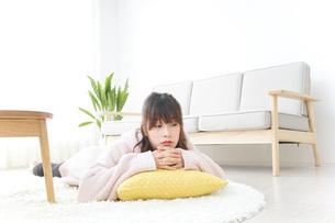 部屋でリラックスをする若い女性の写真素材 [FYI04700482]
