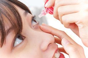 目薬を入れる若い女性の写真素材 [FYI04700610]