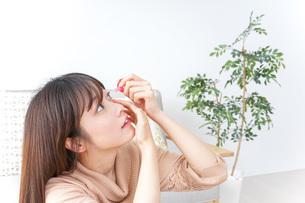 目薬を入れる若い女性の写真素材 [FYI04700621]