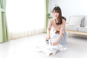 アイロンがけをする若い女性の写真素材 [FYI04700637]