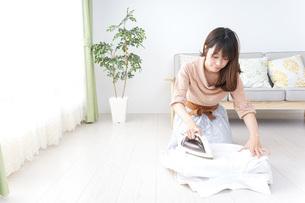 アイロンがけをする若い女性の写真素材 [FYI04700639]