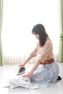 アイロンがけをする若い女性の写真素材 [FYI04700648]