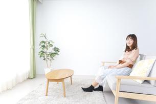 部屋でリラックスをする若い女性の写真素材 [FYI04700653]