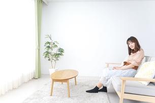 部屋でリラックスをする若い女性の写真素材 [FYI04700654]