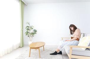 部屋でリラックスをする若い女性の写真素材 [FYI04700656]