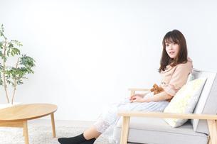 部屋でリラックスをする若い女性の写真素材 [FYI04700666]