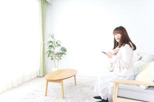部屋でリラックスをする若い女性の写真素材 [FYI04700676]