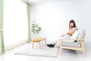 部屋でリラックスをする若い女性の写真素材 [FYI04700677]
