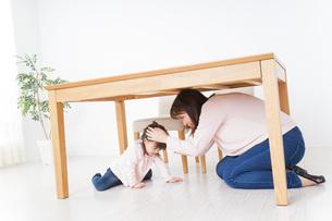 机の下に避難する親子の写真素材 [FYI04701341]