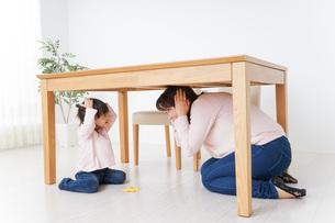 机の下に避難する親子の写真素材 [FYI04701342]