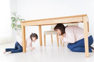 机の下に避難する親子の写真素材 [FYI04701346]
