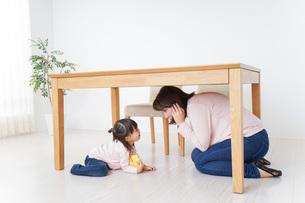 机の下に避難する親子の写真素材 [FYI04701352]