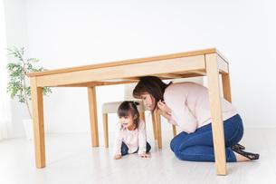 机の下に避難する親子の写真素材 [FYI04701353]