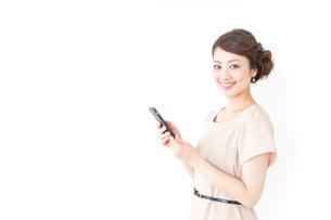 スマホを使うおしゃれ着の女性の写真素材 [FYI04701473]