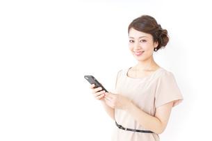 スマホを使うおしゃれ着の女性の写真素材 [FYI04701477]