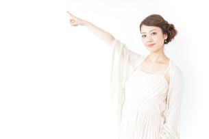 ドレス姿で上を差す女性の写真素材 [FYI04701605]