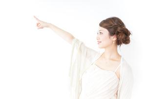 ドレス姿で上を差す女性の写真素材 [FYI04701607]
