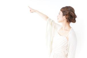ドレス姿で上を差す女性の写真素材 [FYI04701608]