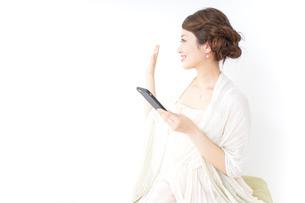 スマホを使うおしゃれ着の女性の写真素材 [FYI04701644]